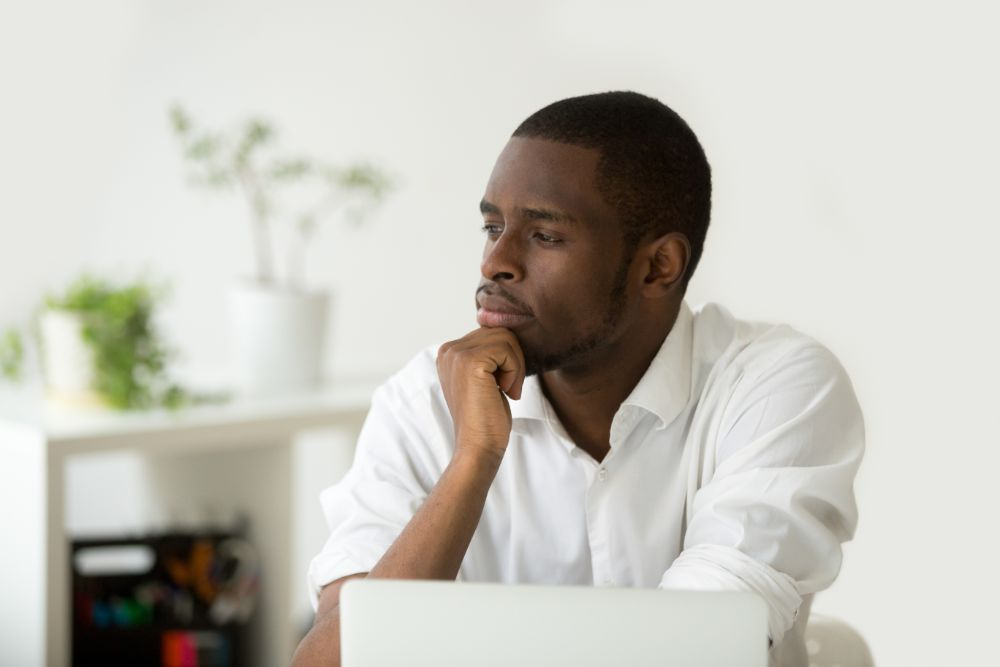 man contemplating while sitting at desk